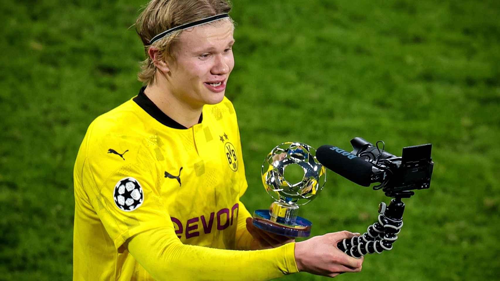 Erling Haaland con el trofeo de mejor jugador del partido de la Champions League y una cámara