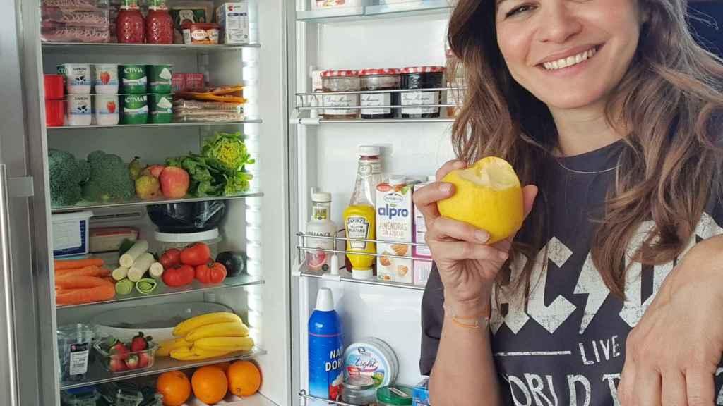 Fabiola Martínez, junto a su nevera, cargada de frutas y verduras.