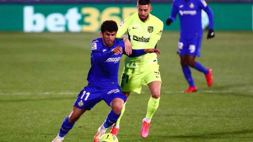 Carles Aleña lucha en carrera con Yannick Carrasco por el balón