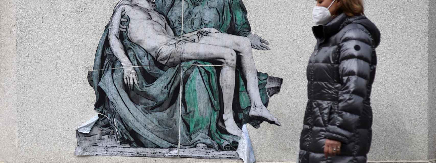 Una mujer con mascarilla pasea ante un mural sobre la Covid en Sofía, Bulgaria.