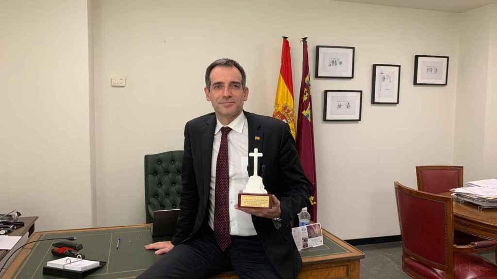Juan José Liarte sujetando una réplica de la cruz de Callosa de Segura en su despacho en la Asamblea Regional.