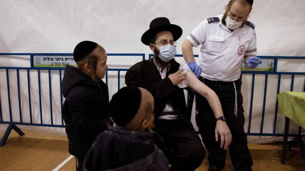 Un judío ultraortodoxo siendo vacunado contra la Covid-19 en Israel.