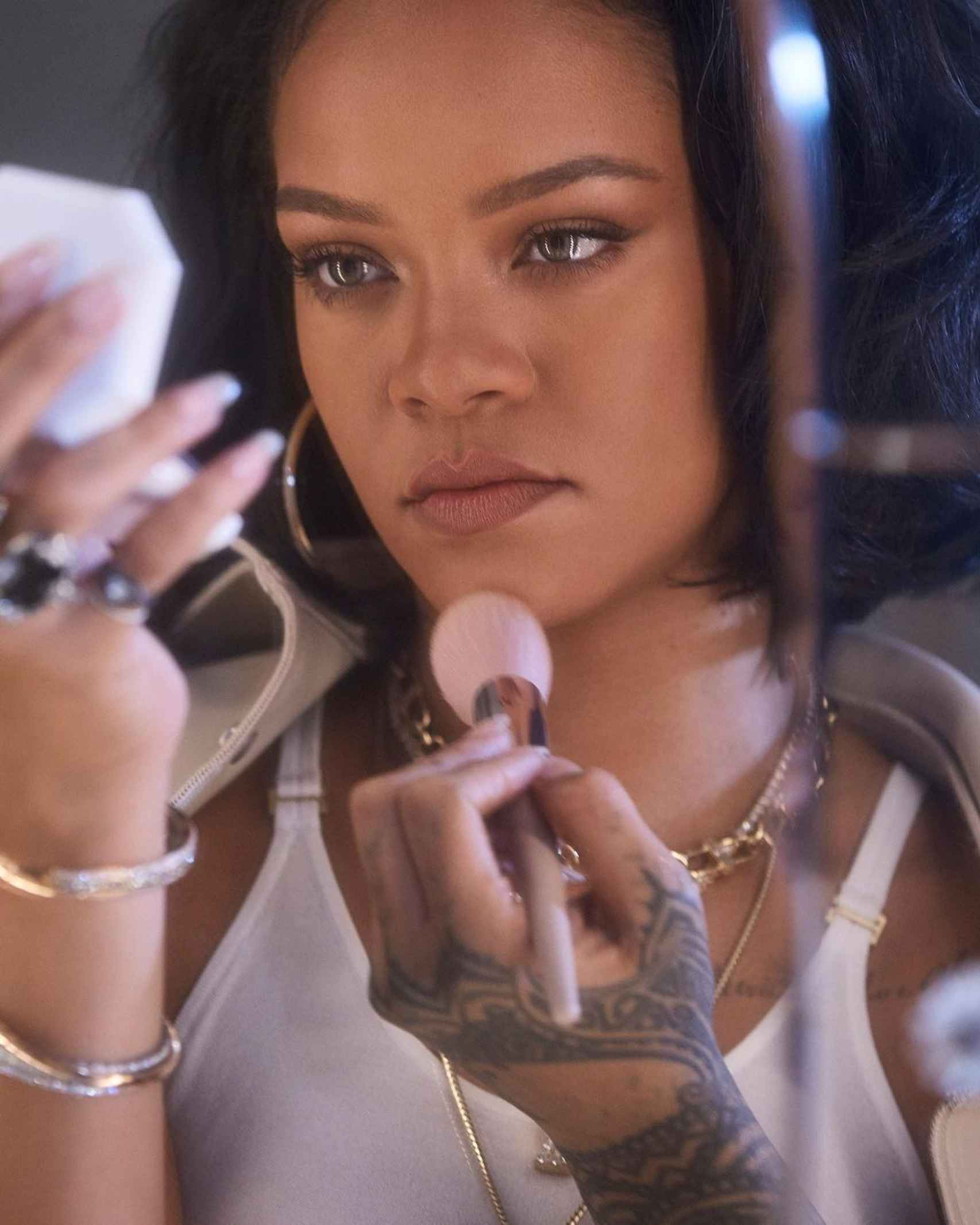 Rihanna, applying makeup with her Fenty Beauty products.