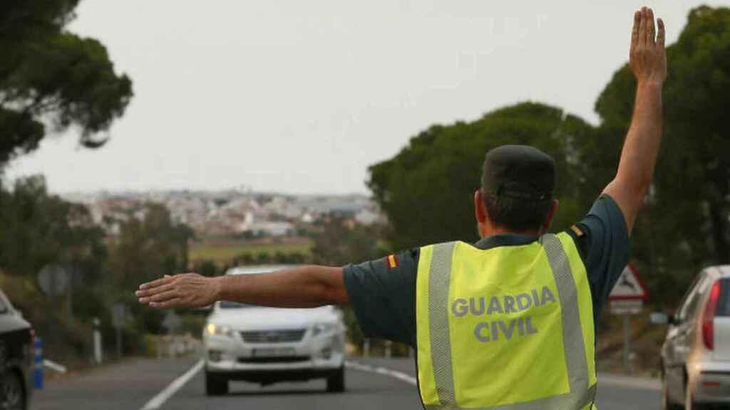 Un agente de la Guardia Civil indica a un coche que se detenga.