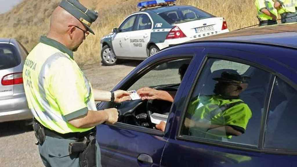 Un agente de la Guardia Civil le pide la documentación a un conductor.
