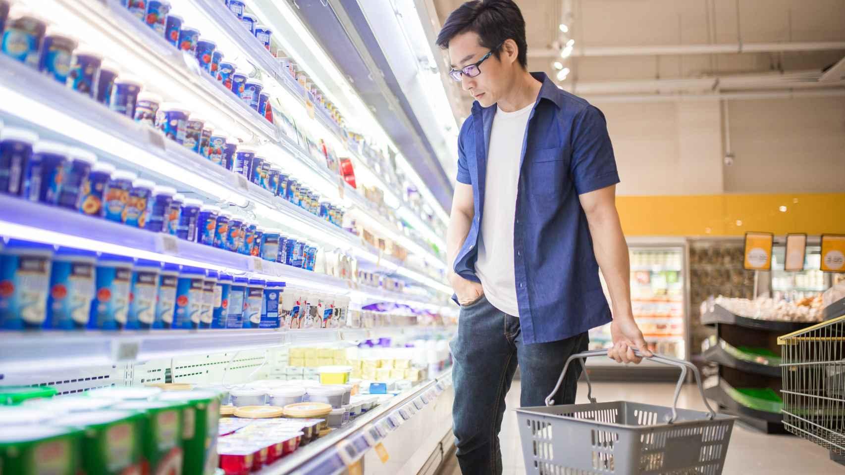 Un hombre busca un yogur entre las estanterías.