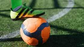 Futbolista sujeta con el pie el balón