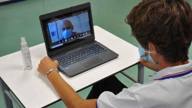 Un alumno en mitad de una clase con mascarilla.