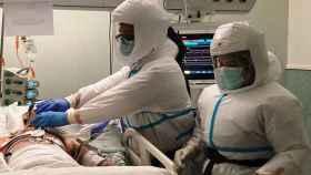Dos profesionales sanitarios atendiendo a un paciente.