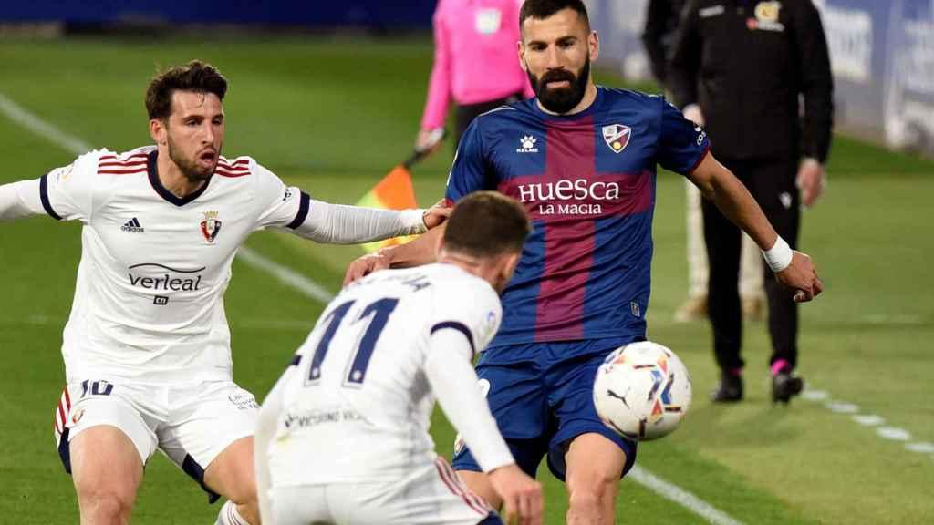 Siovas y Kike Barja pelean por un balón en la banda