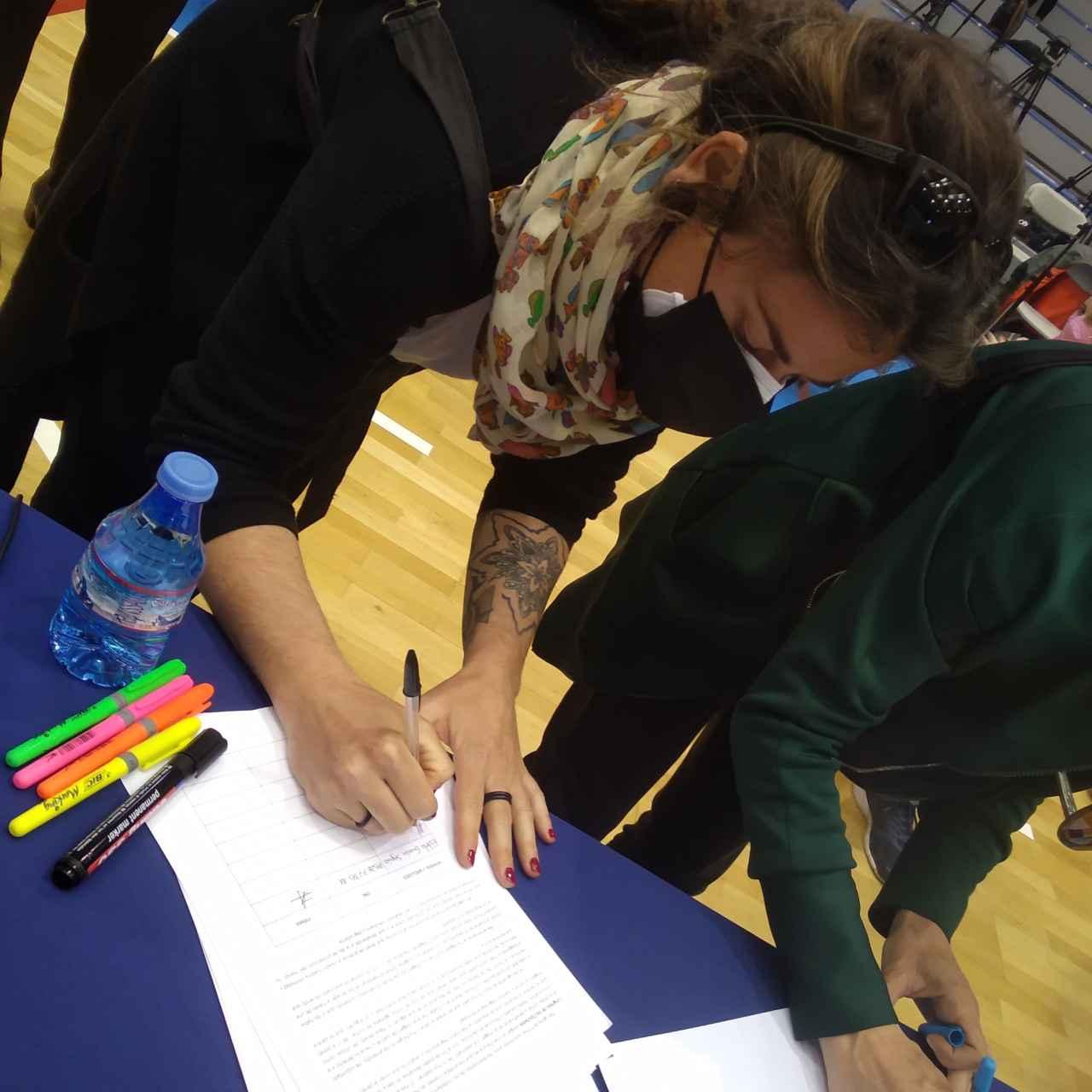 Dos amigas de Patricia estampando su firma en la campaña.