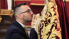 Álvaro Abril, besando la mano de una de las imágenes que arregla.