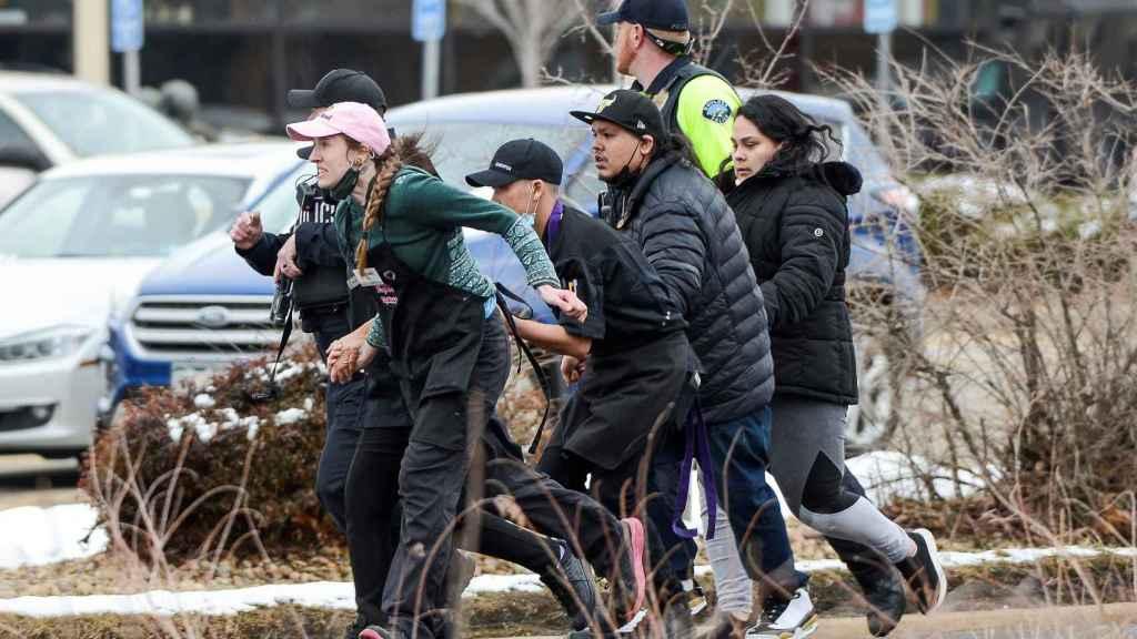 Un grupo de personas huye del lugar del tiroteo en Colorado, EEUU.