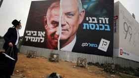 Un judío ultraortodoxo ante un cartel electoral del partido centrista Azul y Blanco, donde aparece Netanyahu (i) enfrentado a Beny Gantz (d).