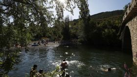 Un grupo de personas disfruta de un baño en el río Arga en la localidad navarra de Irozt.