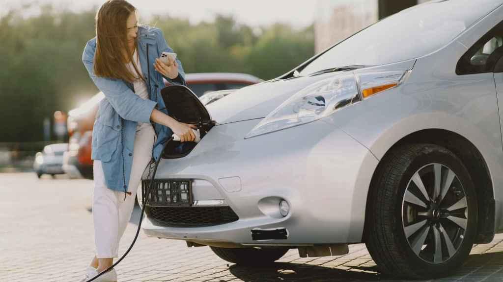 Una mujer cargando un coche eléctrico.