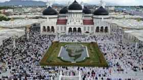 Un grupo de musulmanes reza ante la Gran Mezquita Baiturrahman, en Banda Aceh (Indonesia)