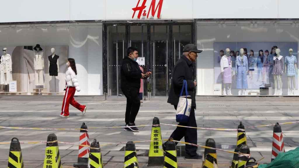 Varios transeuntes pasan ante una tienda de H&M en Hong Kong este pasado viernes.