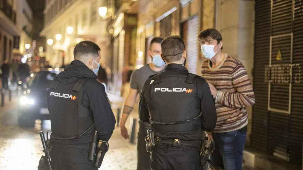 Dos policías increpan a dos turistas.