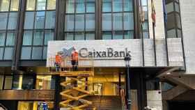 Unos operarios colocan el rótulo de CaixaBank en la antigua sede valenciana de Bankia.