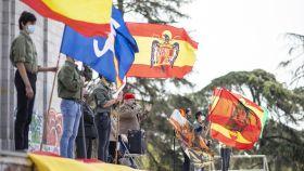 Varios adolescentes miembros de Acción Juvenil Española se manifiestan en el Arco de la Victoria este domingo.