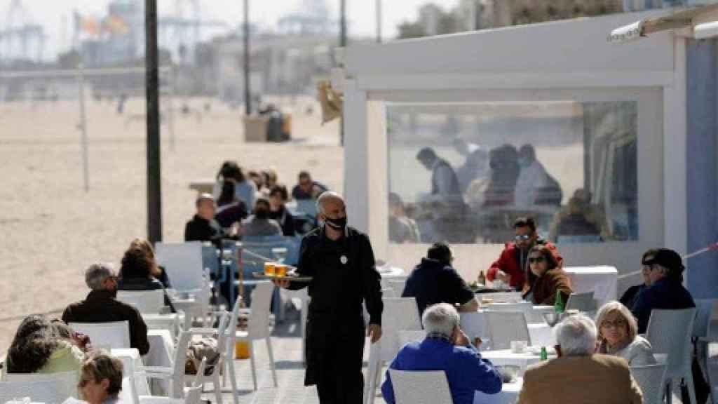 Distintos clientes disfrutan de una terraza en la playa de la Malvarrosa en Valencia.