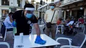 Un camarero limpia la mesa antes de servir al cliente.