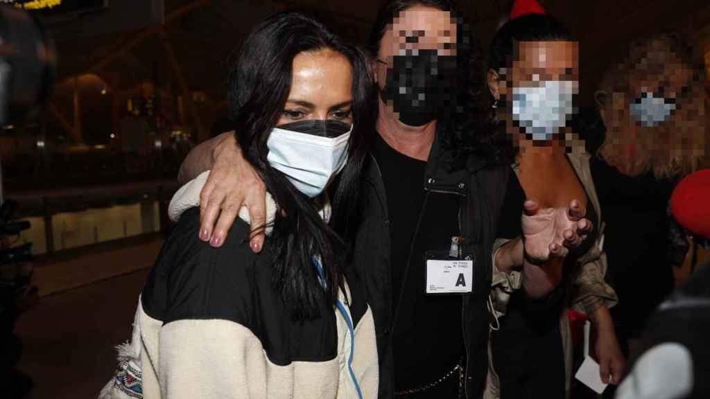Olga Moreno, seria y cabizbaja rodeada de cámaras en el aeropuerto.