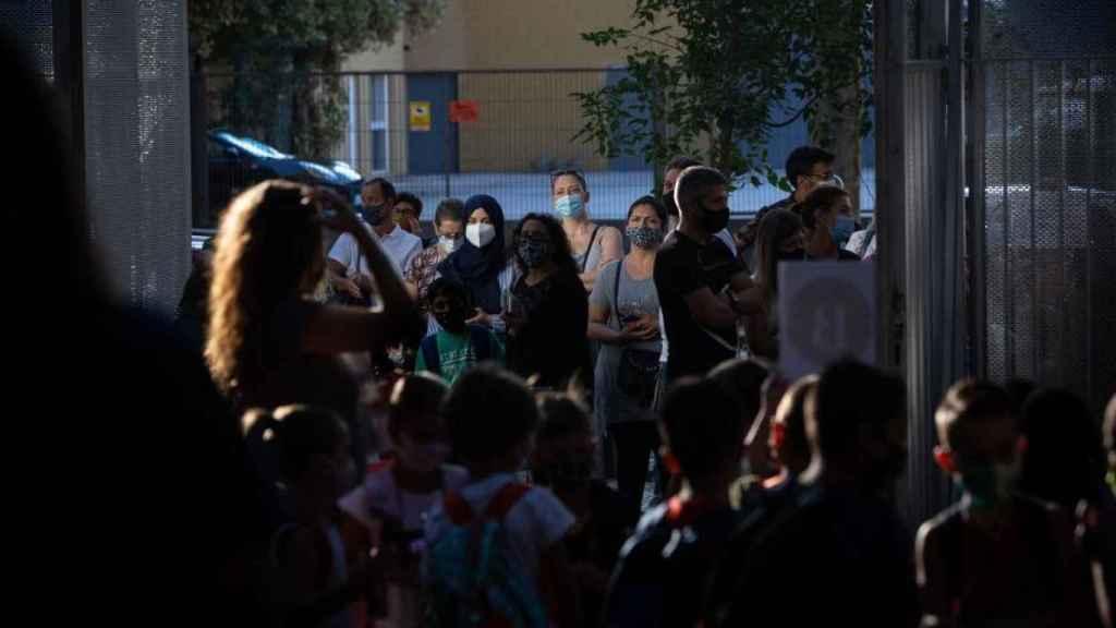 Padres y alumnos esperan a las puertas de un colegio en Cataluña.