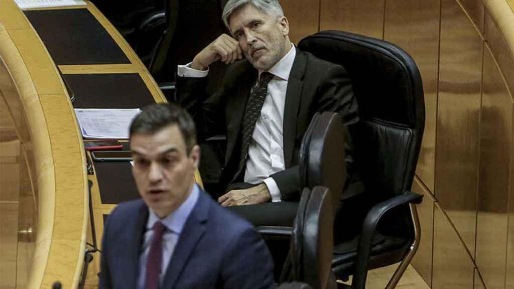 El ministro del Interior, Fernando Grande-Marlaska, escucha la intervención del presidente del Gobierno, Pedro Sánchez, en un pleno en el Senado.