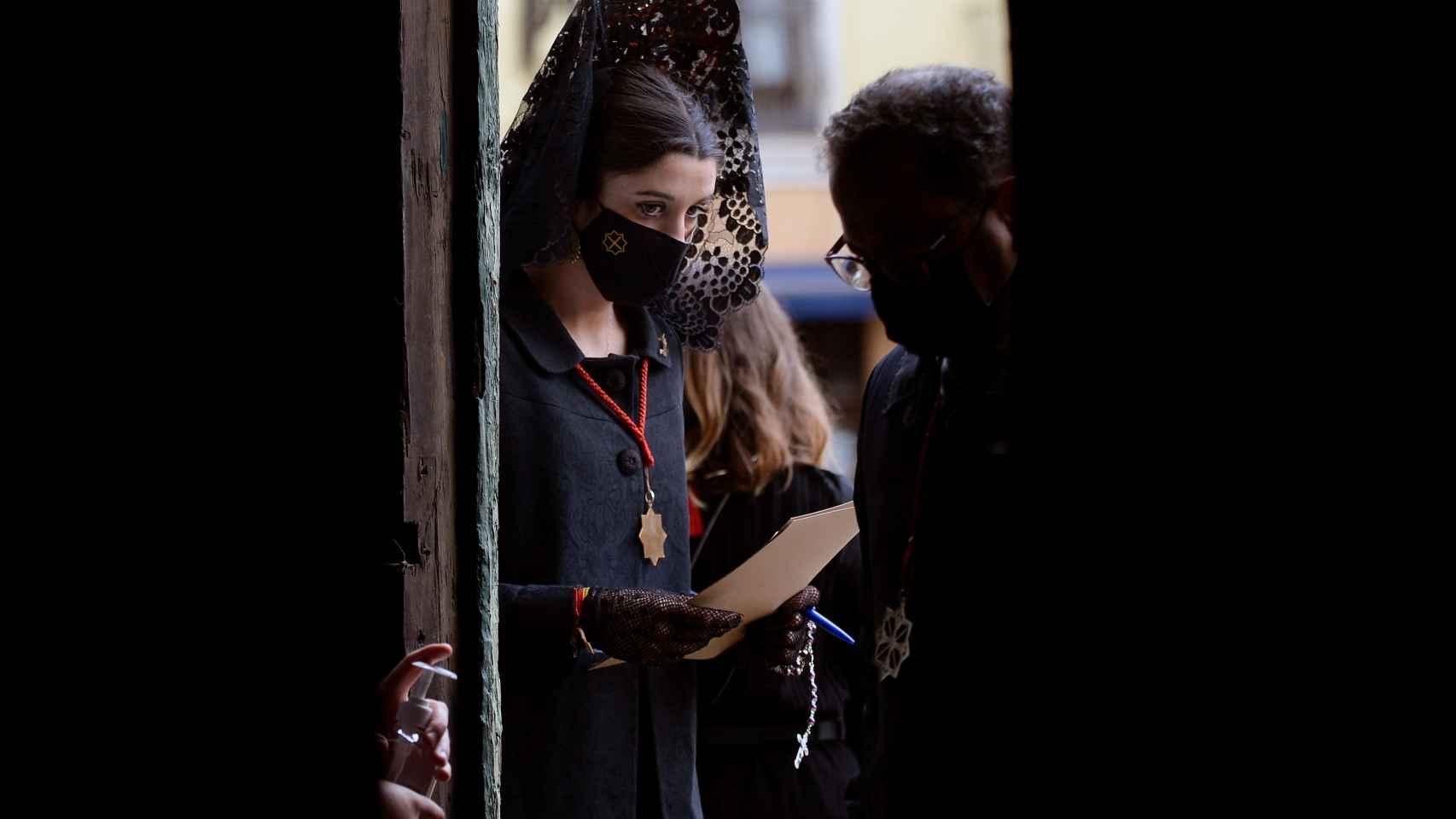 Una mujer vestida de manola controla los accesos a la catedral de Valladolid, donde se ha realizado la lectura del Sermón de las Siete Palabras.