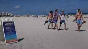 Varias personas caminan por la playa en Miami.