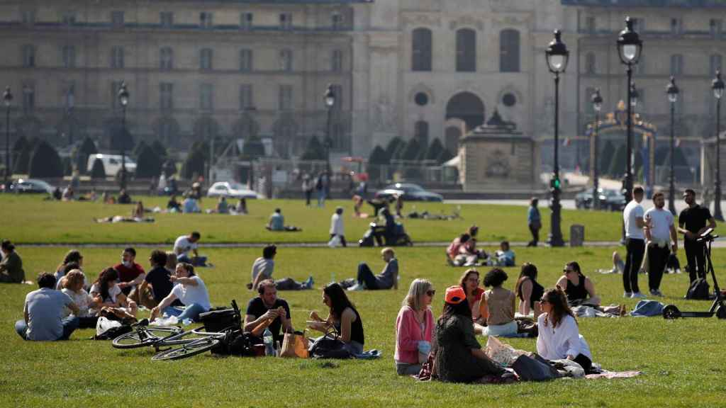Decenas de personas disfrutan del buen tiempo cerca de Los Inválidos, en París.
