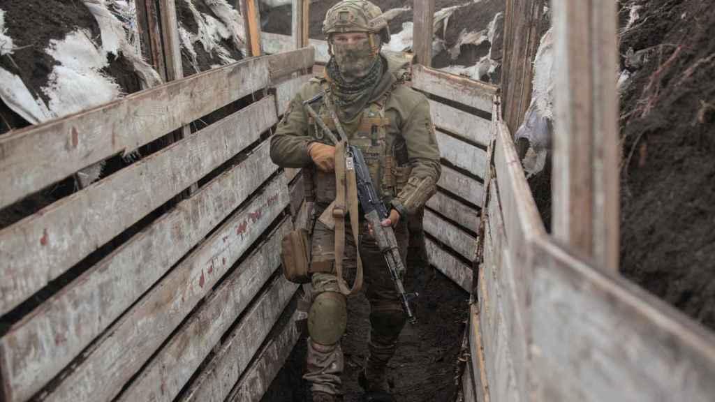 Un miembro de las fuerzas armadas ucranianas camina entre trincheras.
