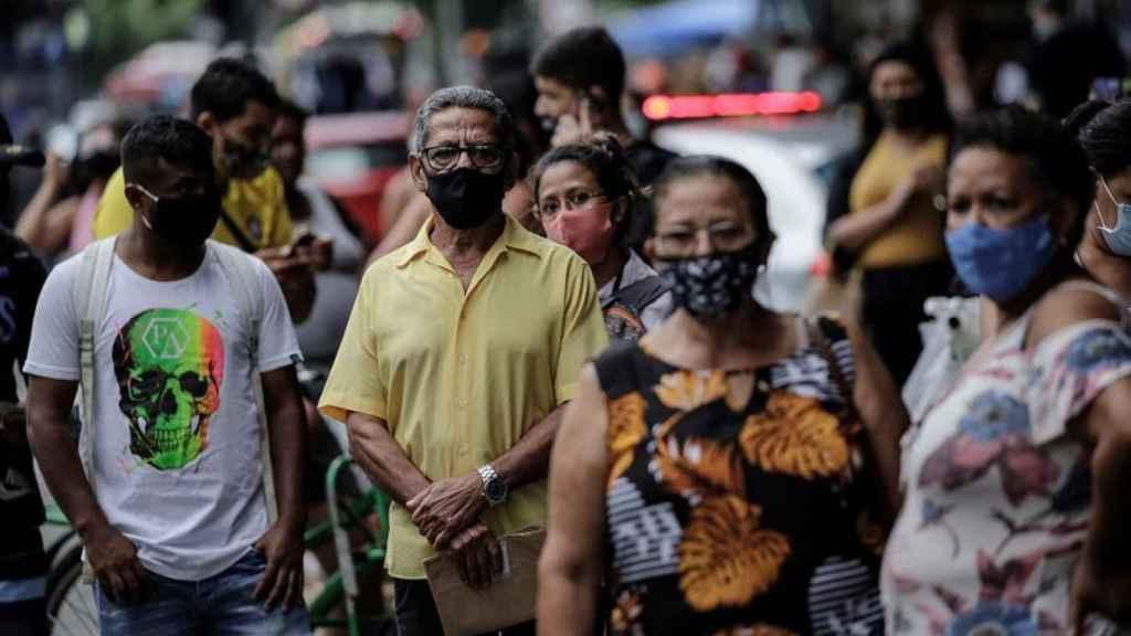 Decenas de personas esperan un autobú en la ciudad de Río de Janeiro.