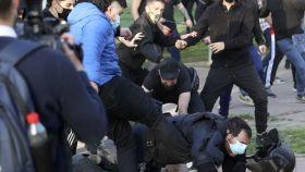 Un radical de izquierdas patea a un antidisturbios durante el acto de Vox en Vallecas.