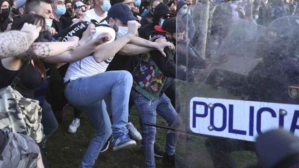 Los manifestantes contrarios al mitin, en un enfrentamiento contra los agentes de Policía.