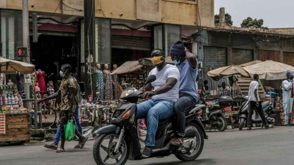 Dos hombres con mascarilla en una moto en Dakar.
