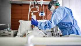 Un médico sujeta un móviles mientras un paciente habla con un familiar en un hospital de Italia. EP