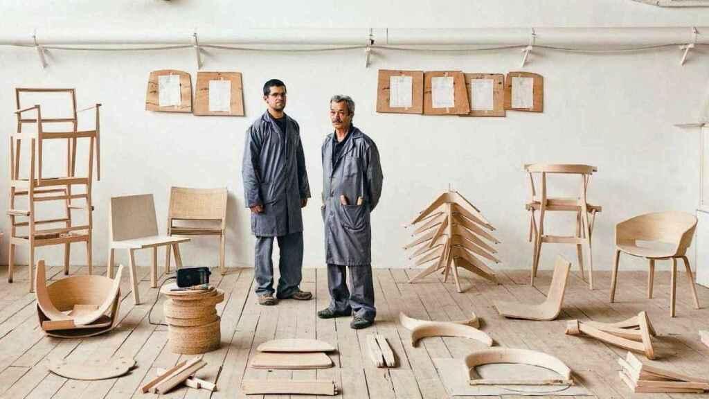 Trabajadores de Andreu World, junto a piezas de madera de sus afamadas sillas. EE
