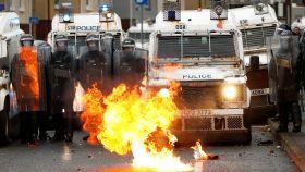 Policías frente a un fuego en Belfast.