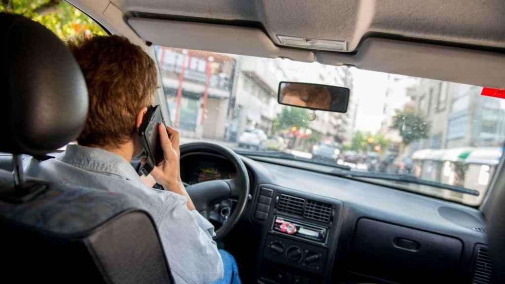 Un conductor utilizando el teléfono móvil en su coche.
