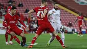 Karim Benzema intenta entrar en el área del Liverpool y es presionado por Nathaniel Phillips