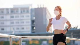 Una joven con una mascarilla mientras hace running.