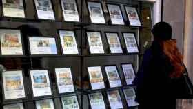 Una mujer mira ofertas de piso en una inmobiliaria.