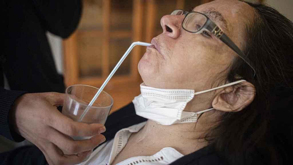 María Isabel Ruiz bebe agua con pajita, ayudada por una enfermera, este miércoles.