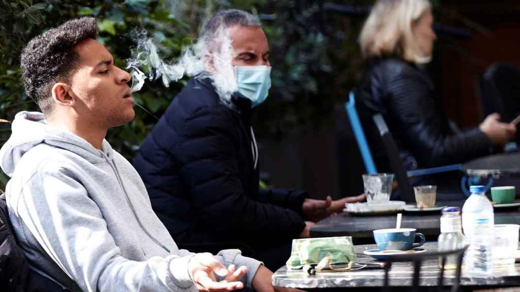 Un joven fumando en un bar de Barcelona.