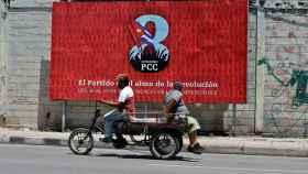 Dos personas pasan frente a una valla que promociona el VIII Congreso del Partido Comunista de Cuba.