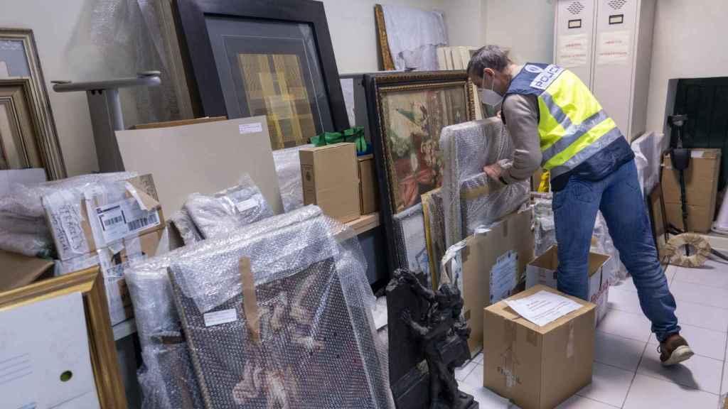 Antonio López manipula uno de los cuadros falsos que guarda en su almacén.
