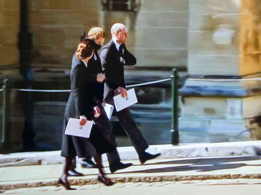 Los príncipes Guillermo y Harry hablando a la salida del sepelio. A su lado, Kate Middleton.